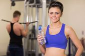 image of lats  - Portrait of a sporty young woman with water bottle while man using lat machine in the gym - JPG