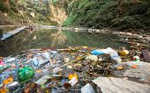 Plastic Contamination into Nature. Garbage and bottles floating on water. Environmental pollution in