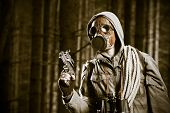 picture of chemical weapon  - Soldier wearing a gas mask is fighting in a forest - JPG