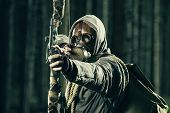 stock photo of doomsday  - A male bow hunter wearing gas mask draws back on his bow - JPG