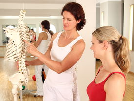stock photo of herniated disc  - Physiotherapist explaining the spine to an female patient  - JPG