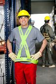 stock photo of hand-barrow  - Portrait of happy mid adult foreman with hands on hips and coworker pushing handtruck at warehouse - JPG