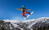 stock photo of ninja  - Snowboarder jumping high in the air with the board like ninja - JPG