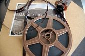 image of yesteryear  - A reel of movie film and a roll of camera film on top of an album - JPG