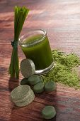 stock photo of chlorella  - Chlorella spirulina and wheatgrass on brown wooden background - JPG