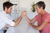 stock photo of wrestling  - Casual business team arm wrestling at desk in the office - JPG