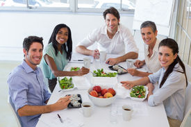 image of half-dressed  - Workers smile at camera while eating healthy lunch in the office - JPG