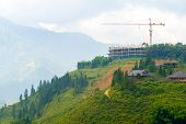 foto of hilltop  - Construction crane building on hilltop that have beautiful view - JPG