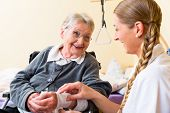 picture of geriatric  - Nurse taking care of senior woman in retirement home bandaging a wound - JPG