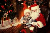 stock photo of christmas claus  - Santa Claus and happy boy sitting in Christmas room and reading a book - JPG