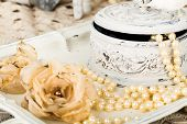picture of lace  - antique jewelry box with pearls on ladies dressing table with shabby chic pearl necklace and lace