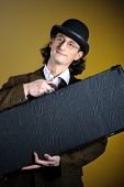 Постер, плакат: Портрет молодой английский ретро джентльмен в котелок Холдинг чемодан в виде багажа Жёлтый фон