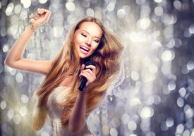 stock photo of karaoke  - Beauty model girl with a microphone singing and dancing over holiday glowing background - JPG