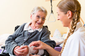 stock photo of nursing  - Nurse taking care of senior woman in retirement home bandaging a wound - JPG