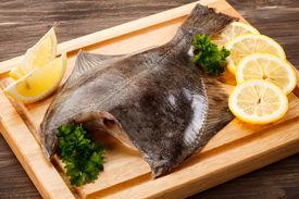 stock photo of flounder  - Fresh raw flounder on cutting board - JPG