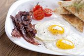 stock photo of bacon  - Delicious fried egg with spices bacon croutons and tomatoes on a white plate. Composition on a wooden table in the background spices and entrees. Photo made by dSLR camera ** Note: Shallow depth of field - JPG