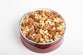 pic of mixed nut  - A festive red tin of deluxe mixed nuts on a white counter - JPG
