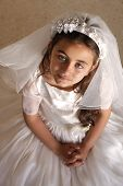 pic of communion  - Child doing her first holy communion dressed in white dress and veil looking at camera praying - JPG