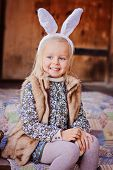 image of country girl  - cute happy child girl wearing bunny ears for easter at country house - JPG