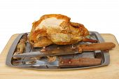 foto of carving  - Carved Guinea fowl on a carving dish with a carving knife and fork - JPG
