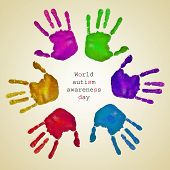 picture of autism  - some handprints of different colors forming a circle on a beige background and the text world autism awareness day written inside - JPG
