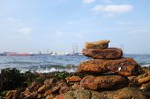 stock photo of shipyard  - Rocks on the coast of the sea with shipyard as background - JPG