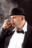 image of bowler  - man with a bowler hat and bow tie drink whiskey - JPG