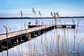 stock photo of tall grass  - Pier for pleasure and fishing boats on shore of Lake Ladoga in Karelia - JPG