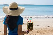 image of pina-colada  - Closeup portrait woman in blue shirt and brown hat holding pina colada rum pineapple mixed drink with straw and tiny umbrella while looking out towards beach and ocean - JPG
