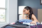 stock photo of grieving  - Closeup portrait young woman having trouble packing suitcase bag sitting on bed hand on face concerned not ready isolated indoors room background - JPG