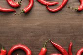 stock photo of red hot chilli peppers  - red hot chilli peppers on the wooden table with copy space - JPG