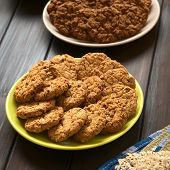 stock photo of cookie  - Oatmeal and apple cookies on plate with chocolate oatmeal cookies in the back photographed with natural light  - JPG