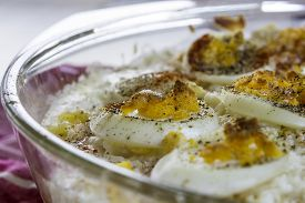 stock photo of pyrex  - Boiled polenta and eggs in a pyrex dish - JPG