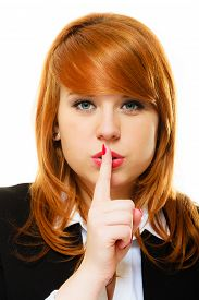 picture of hush  - Business woman redhaired girl asking for silence or secrecy with finger on lips hush hand gesture - JPG