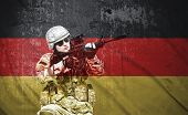 stock photo of rifle  - soldier holding rifle on a Germany flag background double exposure - JPG