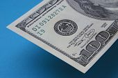 stock photo of one hundred dollar bill  - part of one hundred dollar note on blue - JPG