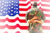 picture of reunited  - Army wife reunited with husband against rippled us flag - JPG