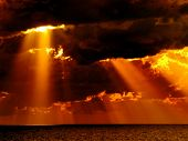 picture of sun rays  - Dark clouds with sun rays over sea - JPG