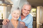 Portrait of cheerful senior man embracing wife at home poster