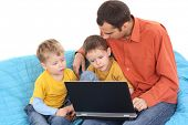 father and two sons having fun with computer game on the sofa