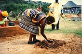 picture of mud-hut  - An African woman with a colorful traditional Ndebele dress preparing red mud to build an African hut - JPG