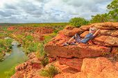 Blonde Woman Resting After Climbing On Red Sandstone Rock At Hawks Head Lookout Over Murchison River poster