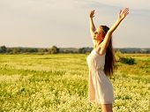 Happy  and serene behavior woman  outdoor with raised hands. Young cheerful girl is on nature over t poster