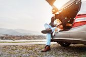Breaded Man In Warm Clothes Siting With Beagle In Car Trunk. Traveling With Pet poster