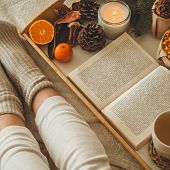 Cozy Winter Evening , Warm Woolen Socks. Woman Is Lying Feet Up On White Shaggy Blanket And Reading  poster