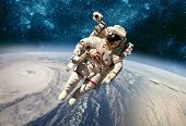 Astronaut in outer space against the backdrop of the planet earth. Typhoon over planet Earth. Elemen poster