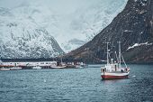 Ship fishing boat in Hamnoy fishing village on Lofoten Islands, Norway with red rorbu houses. With f poster