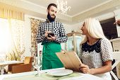 Smiling Bearded Young Waiter Taking Order In Cafe. Man Taking Order From Girl In Cafe. Waiter Servin poster
