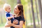 Mom And Baby Together. Young Mother Hugs Son. Woman With A Child Walking In The Park. Maternal Love  poster