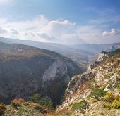 Autumn morning mountain view with sunbeam and haze into canyon. poster